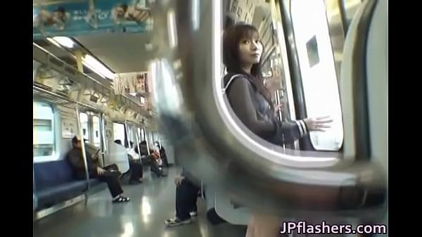 女子校生動画。野外露出 すけすけセーラー服に白い紐パンビキニの女子校生が電車の中で扉の前に立ちながらカメラマンと会話