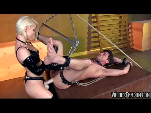 Доминирующая блондинка страпоном трахает в жопу подвешенного раба
